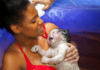 Young black mom holding newborn after waterbirth