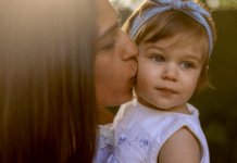 Little girl kissed on cheek by mom