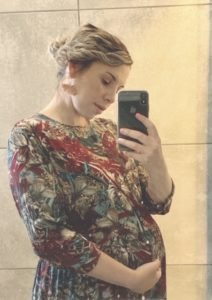 Pregnant woman in floral dress taking selfie