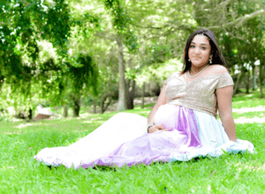 Pregnant woman posing on grass for photo