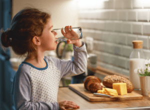 Child drinking glass of water in kitchen