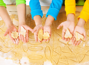 Preschoolers hands holding out cookie dough shapes