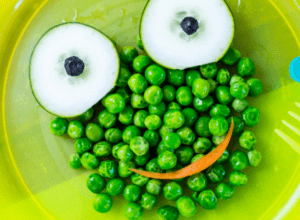 Peas, carrot and cucumber used in a smiley face