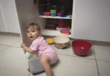 Girl toddler caught in the Tupperware cupboard
