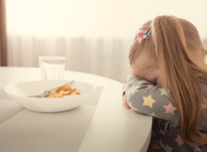 Toddler girl crying at table about food