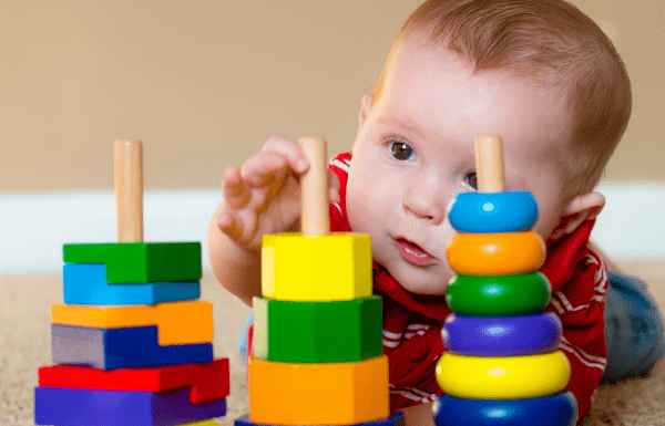 Baby playing with brightly coloured stacking toys