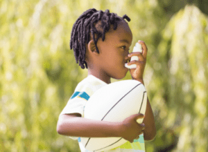 Boy with ball inhaling from asthma pump