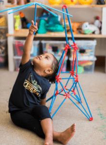 Girl building Eiffel Tower out of sticks