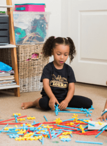 Girl playing with colourful toy sticks
