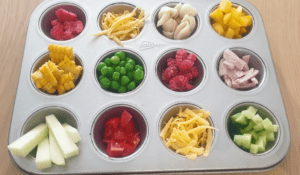 Muffin tray filled with assorted healthy foods