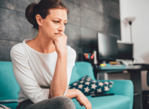 Worried mom on couch suffering from anxiety