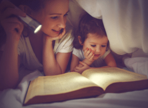 Mom reading to toddler under bed sheet