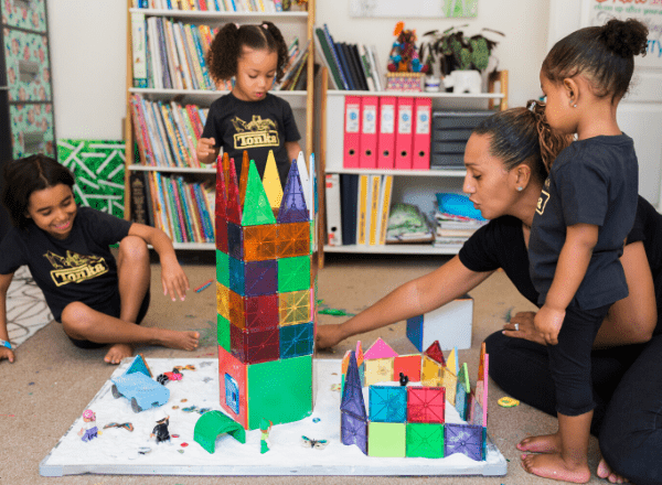 Mom and daughters playing with coloured tiles