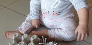 Baby sticking earbuds into empty egg carton