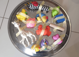 Toy animals taped to round metal tray