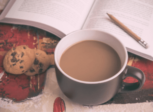Mug of coffee with cookies and book