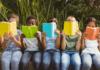 Five children sitting on a bench reading Roald Dahl books