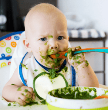 Baby using a spoon to feed himself while practising weaning