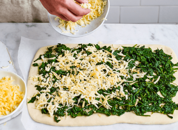 sprinkling the cheese on the pull apart spinach and cheese bread recipe