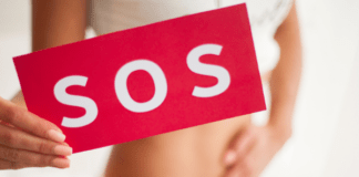woman holding her abdomen and a sign saying SOS because she has a urinary tract infection