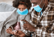 Father and daughter wearing masks and sanitising their hands