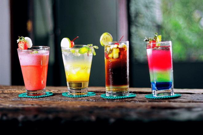 Alcoholic cocktails lined up along a bar counter