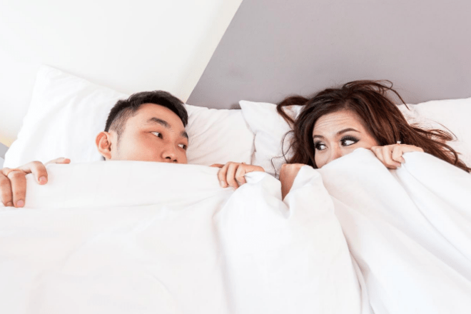 man and woman under a duvet together