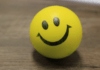 big smiley face on a yellow stress ball