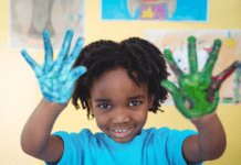 improve your child's gross motor development: child holding up their painted hands
