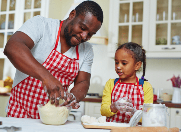 age appropriate kitchen: father and daughter kneading dough together in the kitchen