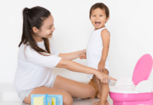 Mom and child standing near a potty while toilet training