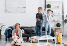 exhausted mom sitting on the floor in the lounge with her kids around her