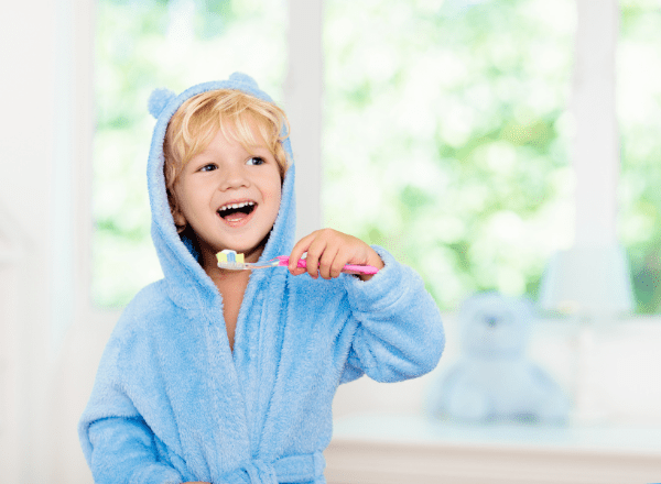 little boy wearing a dressing gown and brushing his teeth