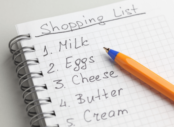 shopping list on a notepad with pen