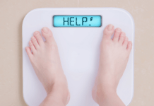 reasons you can't lose belly fat: woman standing on a scale that says help