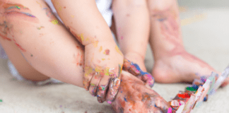 Why messy play is critical to your babys development and 5 activities to try: baby's feet covered in paint