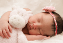 baby sleeping with security blanket stuffed animal or lovey