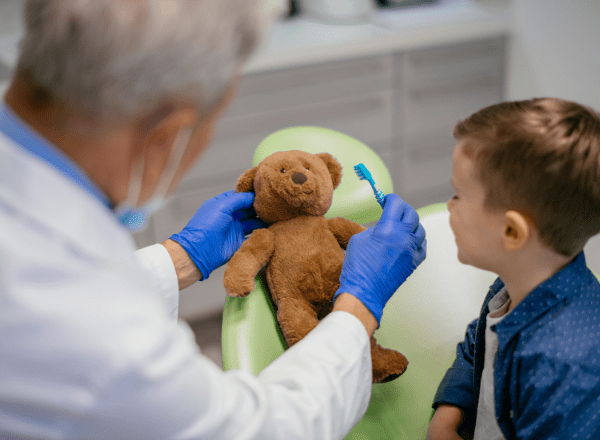 when should you take your child to the dentist for the first time: child at dentist with teddy bear having its teeth cleaned