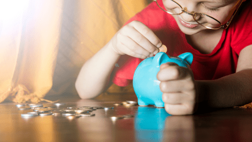 activities to keep kids busy at home that are also good for their development: child putting money into piggy bank