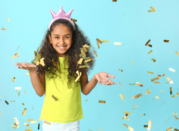 how to raise children to be confident with a healthy body image: young girl wearing a crown with gold confetti