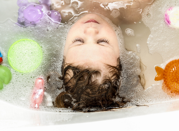 how to wash your toddler's hair without tantrum or crying: little girl washing her hair in the bath