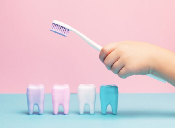 how to choose the right toothbrush and toothpaste for your child: child holding a toothbrush