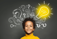 boy with lightbulb in front of a blackboard: speech development in children causes for delay normal milestones