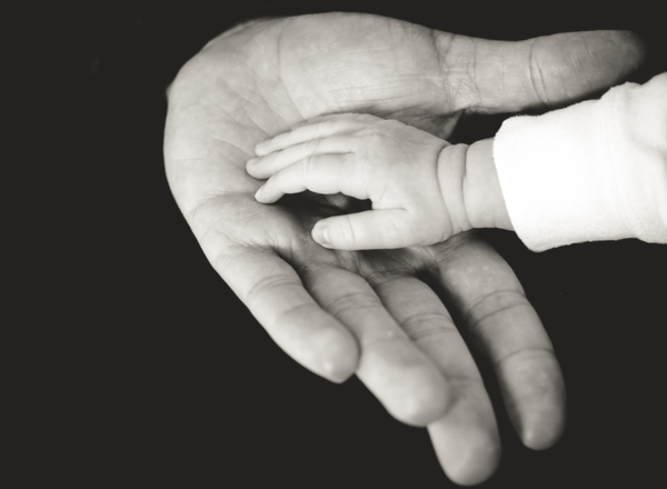 flying with newborn south africa: baby adult hands touch