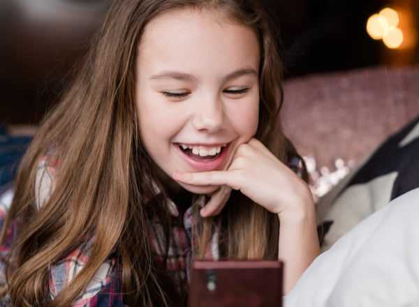 young girl with a smartphone: at what age should you give your child a phone