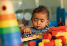 child playing with blocks: gross motor skills in babies milestones by age