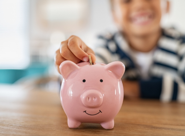 child putting money into a piggy bank: how to talk to your children about money so that they can understand