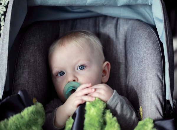 road trip with toddlers in south africa: toddler car seat buckled pacifier