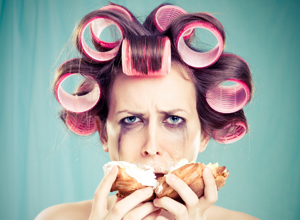 woman crying and eating a donut: foods to eat and avoid during pms and your period