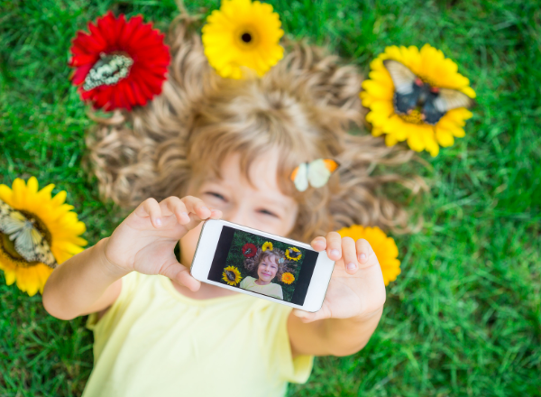 young girl taking a selfie: the effect social media filters and photoshop have on childrens self esteem